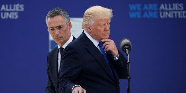 U.S. President Donald Trump reacts as he speaks beside NATO Secretary General Jens Stoltenberg at the...