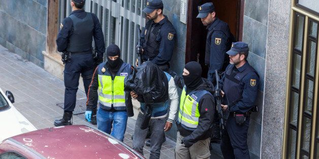 A man (C) suspected of belonging to Islamic State is led by Spanish National Police officers after being...
