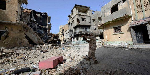 Un membre des forces libyennes pro-gouvernement pendant les combats contre les révolutionnaires libyens,...