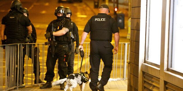 Armed police officers stand near the Manchester Arena, where U.S. singer Ariana Grande had been performing,...