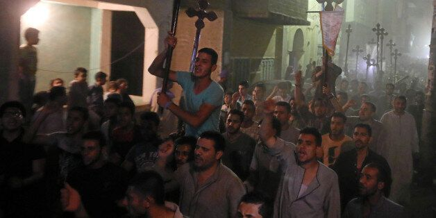 Mourners carry crosses and march after the funeral of at least 28 Coptic Christians who were killed on...