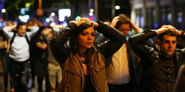 People leave the area with their hands up after an incident near London Bridge in London, Britain June...
