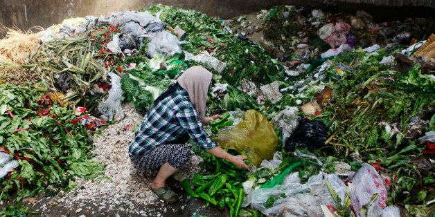 A woman picks up vegetables discarded by food vendors at a garbage dump site of a wholesale market in...