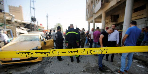 Police tape cordon is seen at the site of a car bomb attack near a government office in Karkh district...