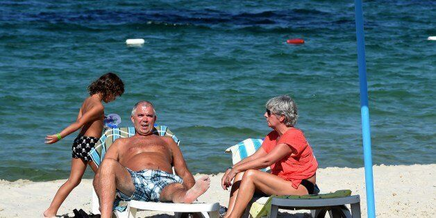 British tourists sit in the sun on July 10, 2015 in the Mouradi Hotel in the touristic Port el Kantaoui,...