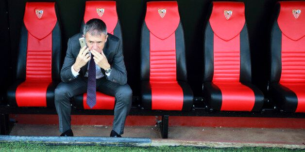 Levante's coach Lucas Alcaraz sits on the bench as he speaks on the mobile phone at the end of their...