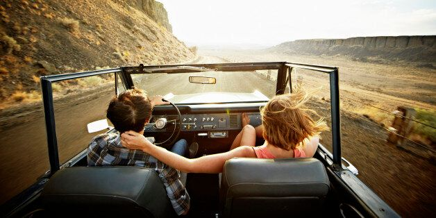 Young couple driving convertible off road vehicle at sunset on desert