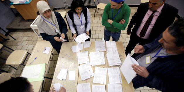 Election workers count ballots at the end of voting for the parliamentary election in Algiers, Algeria,...