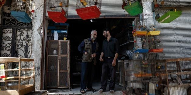 Syrian men chat in front of a shop selling animals in the rebel-held town of Douma, on the eastern outskirts...