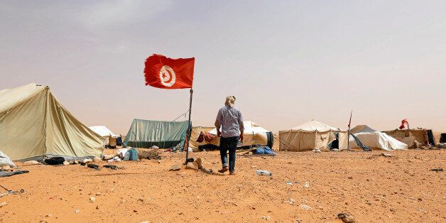 A Tunisian protester walks near his tent during a sit-in at El Kamour oilfield, near the town of Tatouine,...