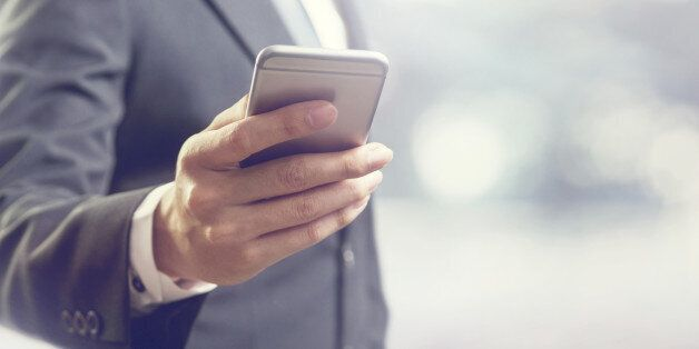 Close up of a business man using mobile smart phone, copy