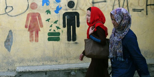 In this Tuesday, March 31, 2015 photo, Afghan university students walk past graffiti, in Kabul, Afghanistan....