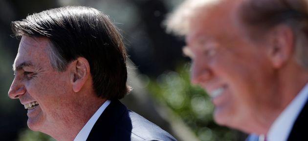 Brazilian President Jair Bolsonaro and U.S. President Donald Trump smile during a joint news conference...