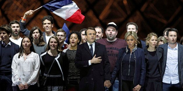 French President elect Emmanuel Macron and his wife Brigitte Trogneux celebrate on the stage at his victory...