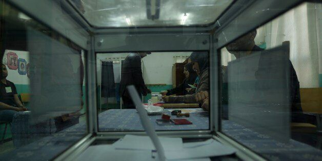 A polling station is seen through a ballot box as a vote in the presidential elections is casted on April...