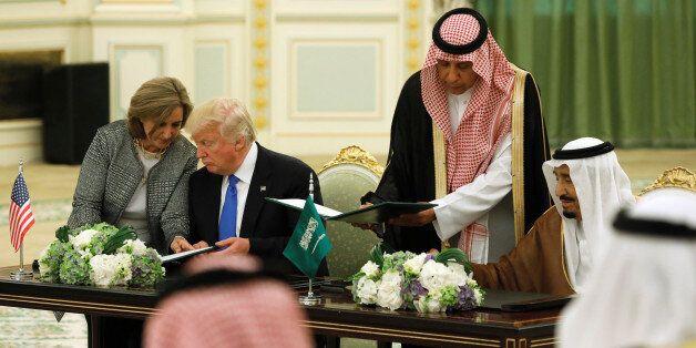 Saudi Arabia's King Salman bin Abdulaziz Al Saud (R) and U.S. President Donald Trump sign a joint security...