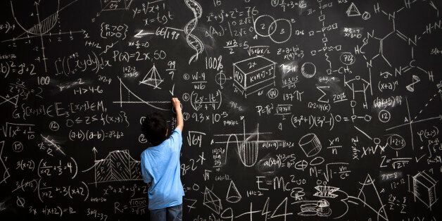 A young boy stands drawing on a huge chalkboard filled with mathematical