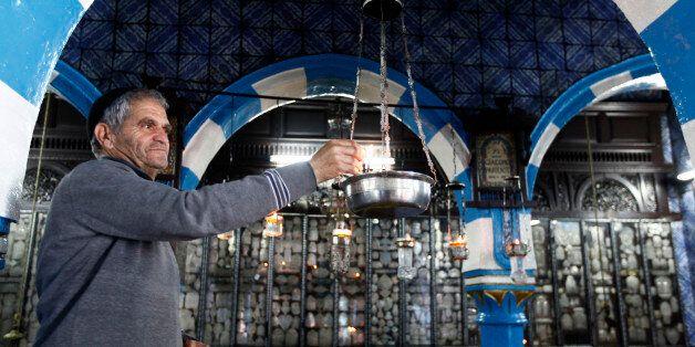 A Jewish man lights candles at the Ghriba synagogue in Djerba May 9, 2012. The Ghriba synagogue in Djerba,...