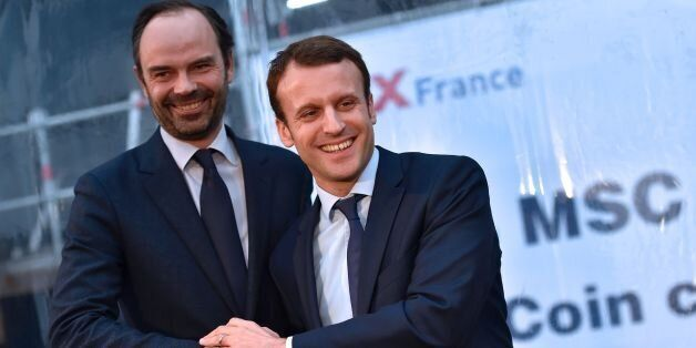 French Economy Minister Emmanuel Macron (R) shakes hand with mayor of Le Havres Edouard Philippe during...