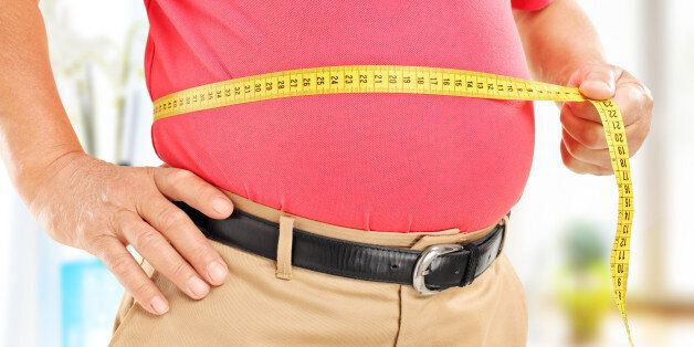 Close-up on a man measuring his belly at