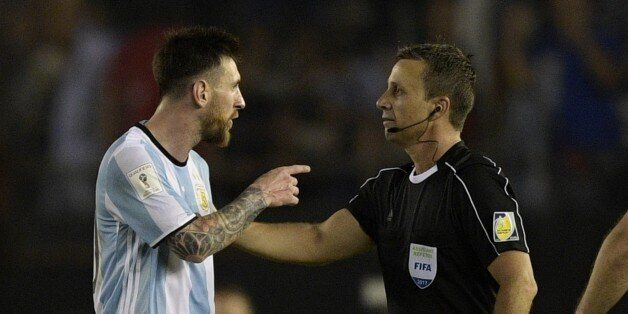 Argentina's forward Lionel Messi (L) argues with first assistant referee Emerson Augusto de Carvalho...