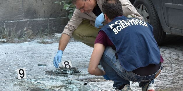 Scientific police works on the site of the explosion of a rudimentary bomb placed between two cars near...