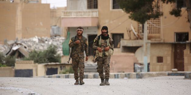 Members of the Syrian Democratic Forces (SDF), walk in the town of Tabqa, about 55 kilometres (35 miles)...