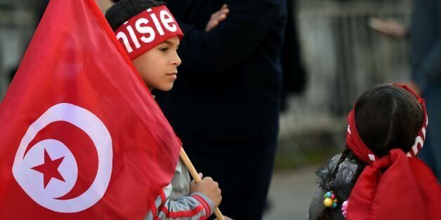 Tunisian children hold their national flags during a rally on January 14, 2016 in the Habib Bourguiba...