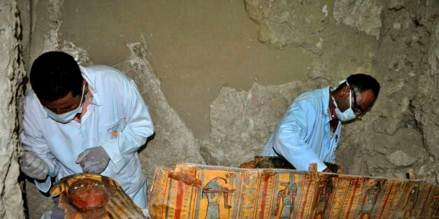 Members of an Egyptian archaeological team work on a wooden coffin discovered in a 3,500-year-old tomb...