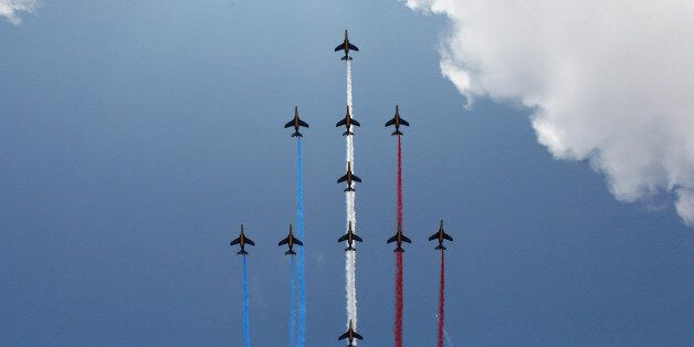 Jets of the Patrouille de France fly over the Champs Elysees avenue during the traditional Bastille Day...
