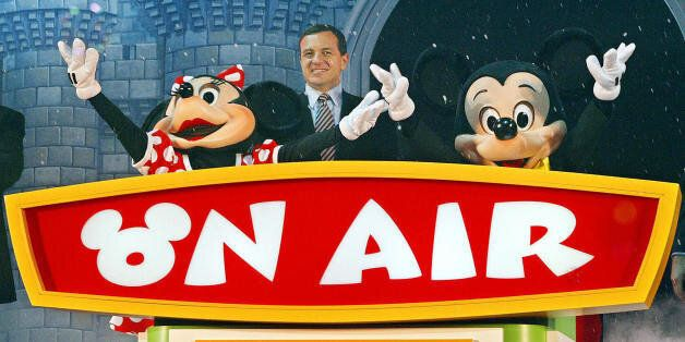 TOKYO, JAPAN: President and chief operating officer Rob Iger (C), Mickey Mouse (R) and Minnie Mouse (L)...