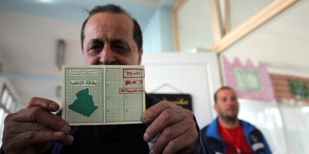 An Algerian man show his electoral card at a polling station in Algiers, Algeria on May 4, 2017 during...