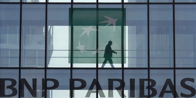 A man is seen in silhouette as he walks behind the logo of BNP Paribas in a building in Issy-les-Moulineaux,...