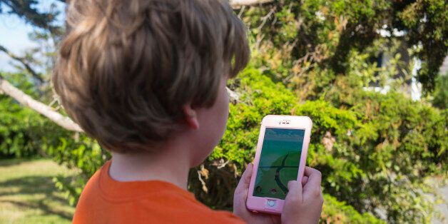 An unidentified boy searches his handset during a search with the Pokémon Go application in East Orleans,...