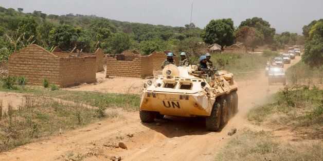 United Nations peacekeeping force vehicles drive by houses destroyed by violence in September, in the...