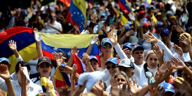Venezuelan opposition activists march in a quiet show of condemnation of the government of President...