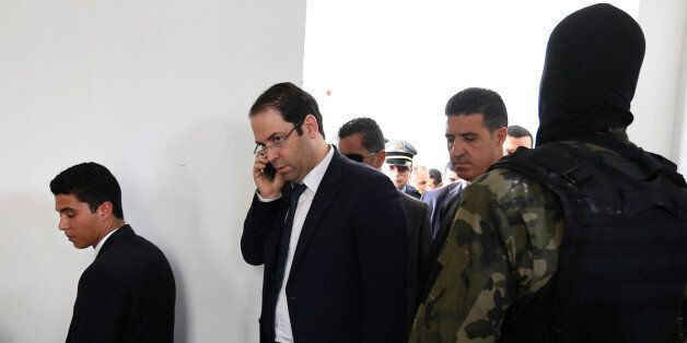 Tunisian Prime Minister Youssef Chahed talks on the phone upon his arrival in the town of Tataouine on...