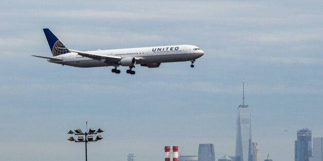 A United Continental Holdings Inc. airplane prepares for landing as the New York City skyline stands...
