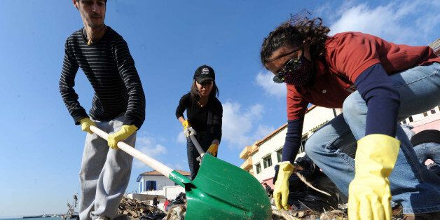 Volunteers collect trash on Tamentfoust beach on January 20, 2012, east of Algiers, during a clean-up...