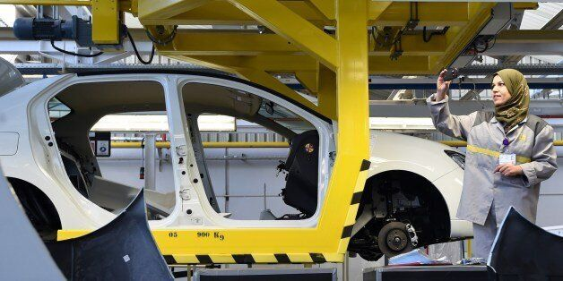 An employee of the French car maker Renault group takes a picture during the inauguration of a new production...