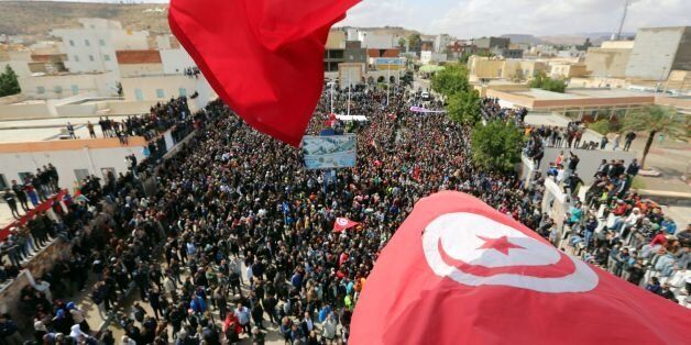 Tunisians wave their national flag as they take part in a general strike against marginalization and...