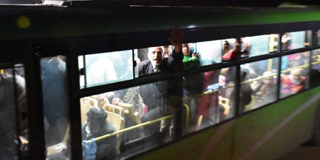 Buses carrying Syrians, evacuated from two besieged government-held towns of Fuaa and Kafraya, arrive...