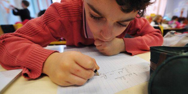 Une élève de CE1 écrit sur son cahier, le 05 décembre 2011 à l'école privée Immaculée Conception...