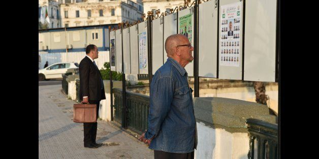 Algerian men look at electorial campaign posters for the upcoming legislative elections in Algiers' Martyrs...