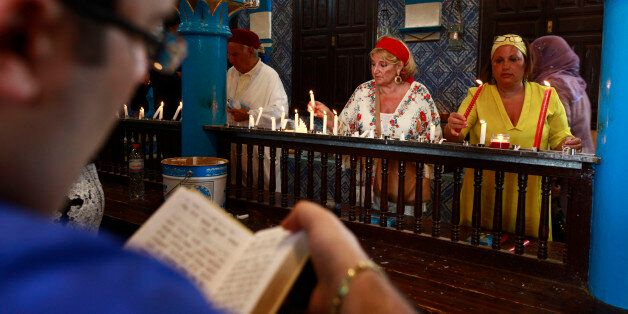 Jewish worshippers light candles inside the El Ghriba synagogue in Djerba, April 28, 2013.Africa's oldest...