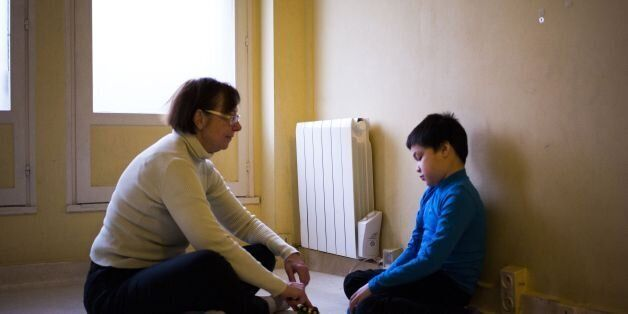 An assistant takes care of Jules, a 8-year-old autistic boy, on March 24, 2017 in Courbevoie, north-west...