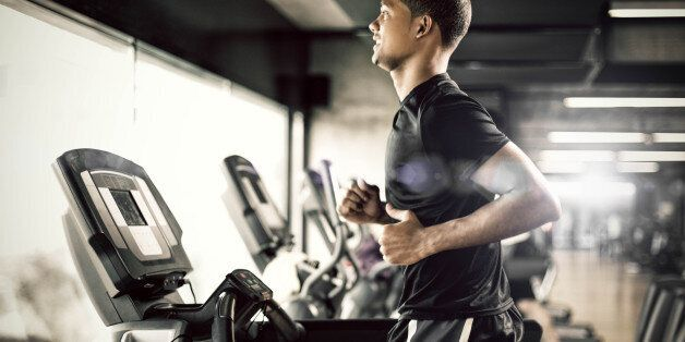Healthy young man in GYM running on