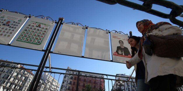 Women walk by electoral campaign posters for the upcoming legislative elections in Algiers centers, Algeria,...