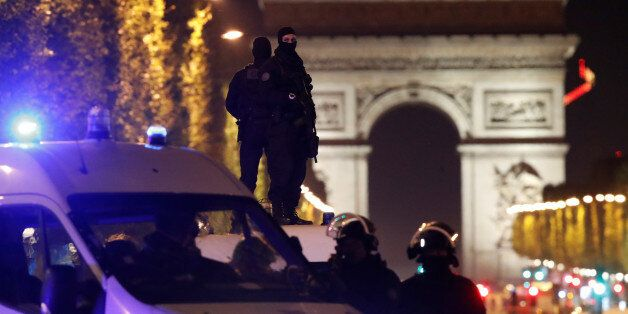 Masked police stand on top of their vehicle on the Champs Elysees Avenue after a policeman was killed...