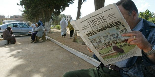 An Algerian reads the 26 May 2003 'Liberte' newspaper titled ' All guilty' 26 May 2003, at the entrance...